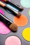 Make-up brushes and colorful eyeshadow palette over black close Royalty Free Stock Photo
