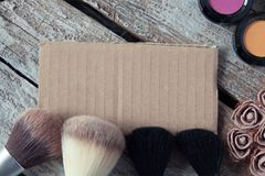 Make up brushes and cosmetic products in close up photo on wooden table stock photos