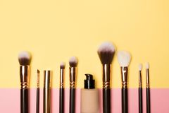 Make up brushes with cosmetic supplies on coloured background royalty free stock photography