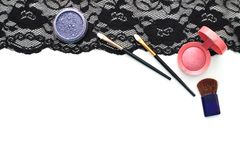 Make-up brushes and cosmetics on black lace Royalty Free Stock Photography