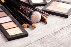 Make up brushes with cosmetics products next to them Royalty Free Stock Photo