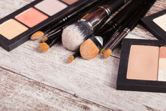 Make up brushes next to cosmetics products Royalty Free Stock Image
