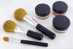 Make-up brushes and powder jars. A set of three make-up brushes and three jars with mineral powder foundation Stock Photo