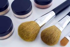 Make-up brushes and powder jars. A set of three make-up brushes and four jars with mineral powder foundation Royalty Free Stock Photo