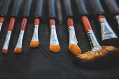 Make-up brushes of shadows in dark case stock image