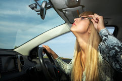 Make-up in car driving Stock Images