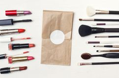 Make up certificate envelope, make-up brushes and lipstick. Make up or visage background. Different cosmetic accessories on white table. Collection of various royalty free stock photography