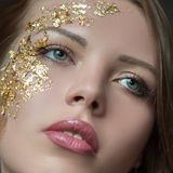 Make-up close-up. Woman`s face, lips, eyes, part. Golden mask. Cosmetics concept stock image