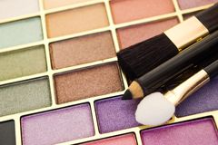 Make-up colors. Cosmetic brush and pencil on paints stock photography