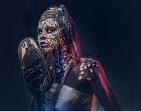 Make-up concept. Portrait of a scary African shaman female with a petrified cracked skin and dreadlocks, holds a. Close-up portrait of an African shaman female Stock Photography