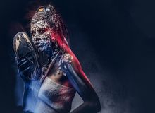 Make-up concept. Portrait of a scary African shaman female with a petrified cracked skin and dreadlocks, holds a. Close-up portrait of an African shaman female Royalty Free Stock Image