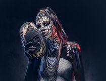 Make-up concept. Portrait of a scary African shaman female with a petrified cracked skin and dreadlocks, holds a. Close-up portrait of a witch from the Royalty Free Stock Photography
