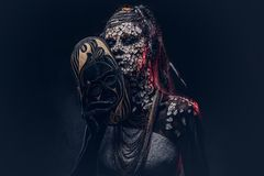 Make-up concept. Portrait of a scary African shaman female with a petrified cracked skin and dreadlocks, holds a. Portrait of a scary African shaman female with Royalty Free Stock Photography