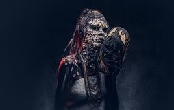 Make-up concept. Portrait of a scary African shaman female with a petrified cracked skin and dreadlocks, holds a. Portrait of a scary African shaman female with Royalty Free Stock Photos