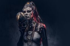 Make-up concept. Portrait of a scary African shaman female with a petrified cracked skin and dreadlocks, holds a. Portrait of a scary African shaman female with Stock Photos