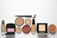 Make-up cosmetics set. Of liquid and cream foundations, compact and loose powder in various tones, bronzing pearls, blush and brush on white background. Top stock photo