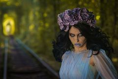 Make up of dead bride in the dress in the tunnel inside a forest with train rails stock photo