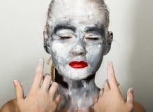 Make-up der abstrakten Kunst Gesichts- und Halsmädchen geschmiert mit grauen Farben und den hellen roten Lippen Holi Festival Lizenzfreie Stockfotos