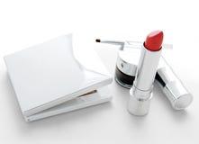 Make-up die met rode lippenstift wordt geplaatst Stock Foto's