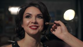 Make-up does make-up on her eyes beautiful bright girl with red lips on the wedding day. Model smiles broadly stock video footage