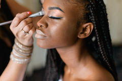 Make up doing make up to african black woman. Beautiful model with braiding. Stock Image