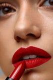 Make-up en schoonheidsmiddelen Vrouwengezicht met Rode Lippen die Lippenstift zetten Royalty-vrije Stock Fotografie