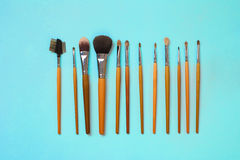 Make up essentials. Set of professional make up brushes on blue background. Place for your text or logo. Ideal for beauty blog Stock Photos