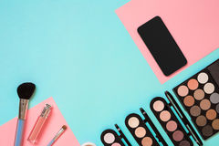 Make up essentials. Set of professional make up brushes, creams and shadows in jars on blue background. Royalty Free Stock Photography