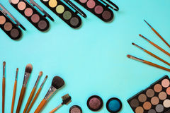 Make up essentials. Set of professional make up brushes, creams and shadows in jars on blue background. Place for your text or logo. Ideal for beauty blog Royalty Free Stock Photography