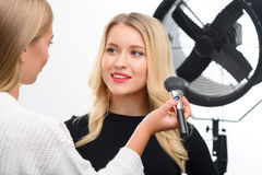 Make up finishing by facial powder apply. Applying face-powder. Appealing young model smiles lightly while facial powder is being applied royalty free stock photo