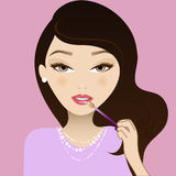 Make up girl. Pretty girl applying lip gloss Royalty Free Stock Photography