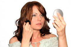 Make up, gray dress series. Girl is using her make up collection in several phases, powder or blush brush Stock Photography
