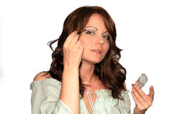 Make up, gray dress series. Girl is using her make up collection in several phases, eyeshadow brush Stock Image