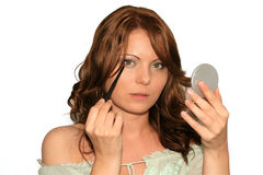 Make up, gray dress series. Girl is using her make up collection in several phases, eye liner Royalty Free Stock Photography