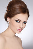 Make-up and hairstyle. Portrait of young beautiful woman with stylish make-up and hair bun Stock Photos