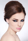 Make-up and hairstyle. Portrait of young beautiful woman with stylish make-up and hair bun Royalty Free Stock Photo