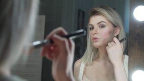 Make-up Junges schönes Mädchen, das Make-up mit Bürste auf Backen macht stock video footage