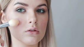 Make-up Junges schönes Mädchen, das Make-up mit Bürste auf Backen macht stock video