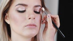 Make-up Junges schönes Mädchen, das Make-up mit Bürste auf Backen macht stock footage