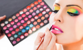 Make-up lipstick. Beautiful women having lipstick applied by make-up artist stock photo