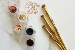 Make it up. Loose eyeshadow containers in neutral colors and gold make up brushes. White marble copy space stock images