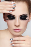 Make-up and manicure. Close-up portrait of young beautiful girl with fancy cat eyes and polka dot manicure stock photography