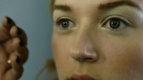The make-up master paints the eyes of the girl. Makes makeup, close-up. stock video footage
