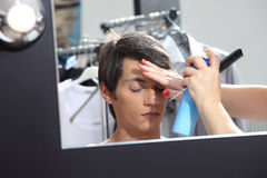Make up model at mirror in dressing room, sprays hair spray Royalty Free Stock Photography