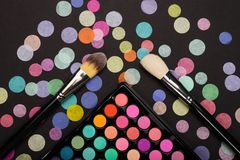 Make-up palette with make-up brushes with colorful confetti on black background. Make-up eyeshadow palette with two make-up brushes on back background with Stock Photos