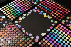 Make-up palettes with scattered colorful confetti on black background with copyspace. Cosmetic make-up palettes with scattered colorful confetti on black royalty free stock photography