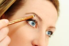 Make up with a pencil. Retouch of a woman face, makeup eyebrow  with a pencil Stock Photography