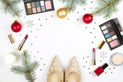 Make up products with Christmas decoration and golden womans shoes on white background with copy space flat lay Stock Photography