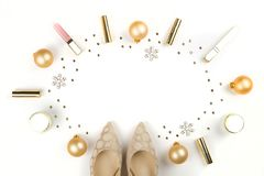 Make up products with Christmas decoration and golden womans shoes on white background with copy space flat lay Stock Image