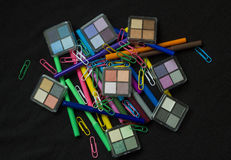 Make up Products with Colourful Pens. And Ppaer Clips on Black Background Royalty Free Stock Photography